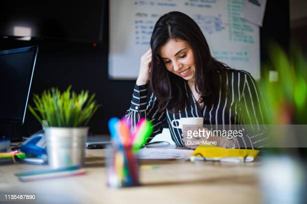 portrait of confident business woman writing document sitting at workplace in office, copy space - publisher stock pictures, royalty-free photos & images