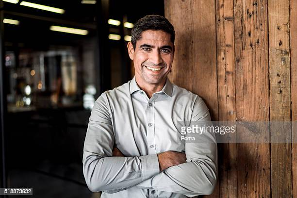 Portrait of confident businessman against wooden wall