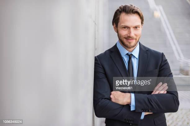 Portrait of confident businessman at concrete wall