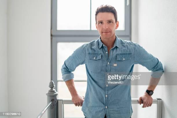 portrait of confident businessman at the window in office - デニムシャツ ストックフォトと画像