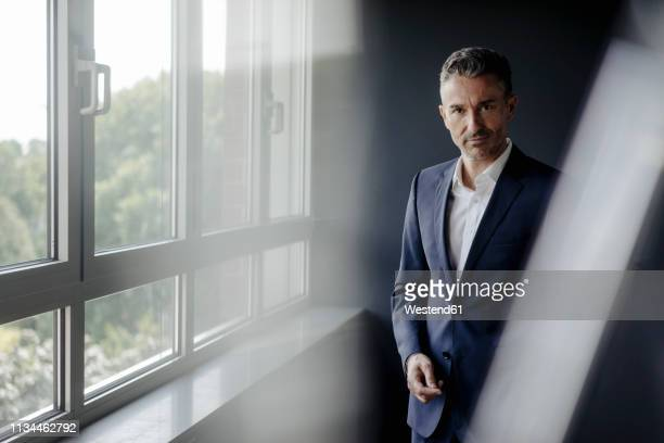 portrait of confident businessman at the window - geschäftskleidung stock-fotos und bilder