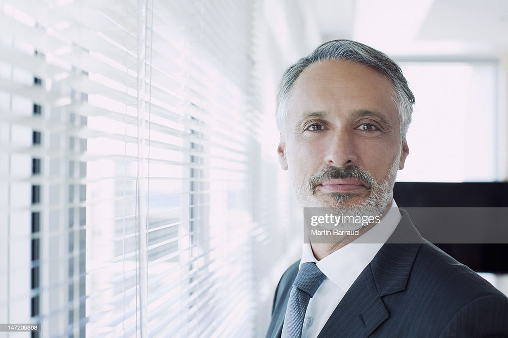 Portrait of confident businessman at window : Stock Photo