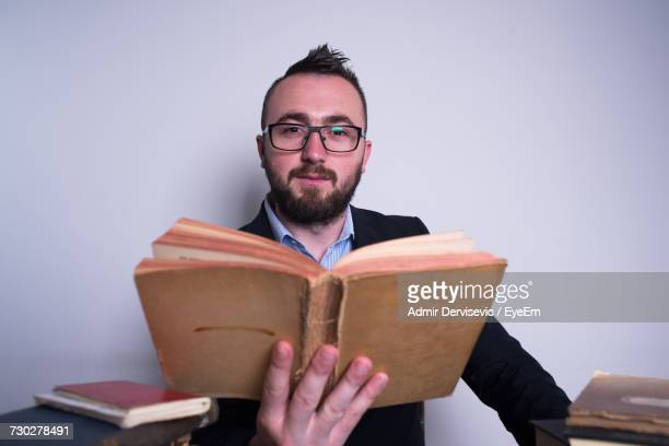 Portrait Of Confident Businessman Holding Book Against Wall