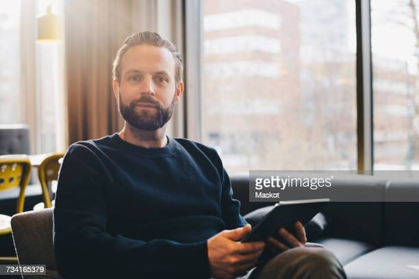 Portrait of confident businessman holding digital tablet at brightly lit office lobby