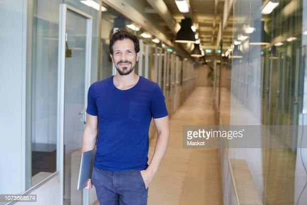 portrait of confident businessman holding laptop while standing at corridor in creative office - handen in de zakken stockfoto's en -beelden
