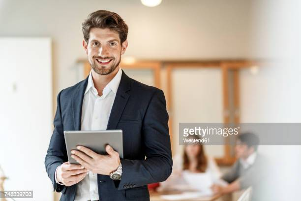 portrait of confident businessman holding tablet with a meeting in background - einzelner mann über 30 stock-fotos und bilder