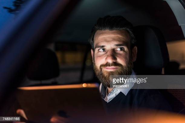 Portrait of confident businessman in car at night