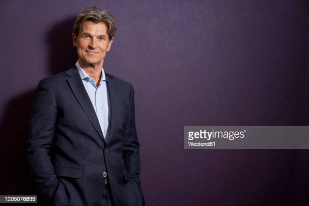 portrait of confident businessman in front of a purple wall - high society stock pictures, royalty-free photos & images