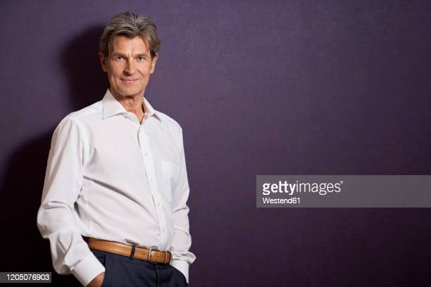 portrait of confident businessman in front of a purple wall - all shirts ストックフォトと画像