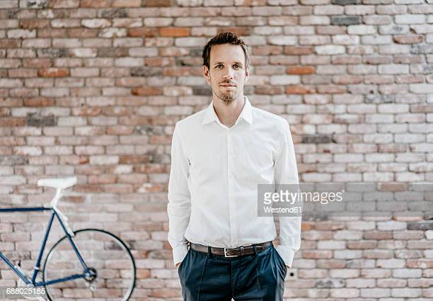 portrait of confident businessman in front of brick wall - vêtement de peau photos et images de collection