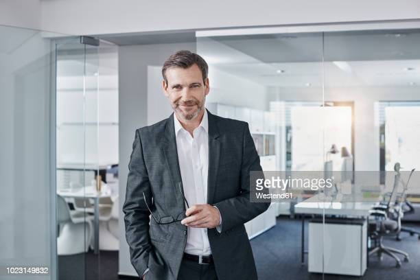 portrait of confident businessman in office - oberkörperaufnahme stock-fotos und bilder