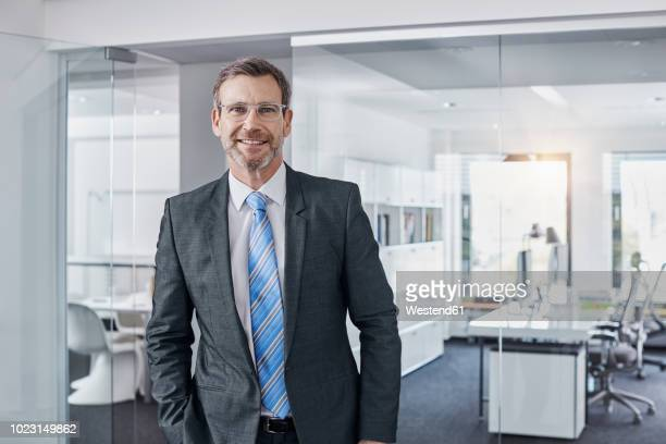 portrait of confident businessman in office - anzug stock-fotos und bilder