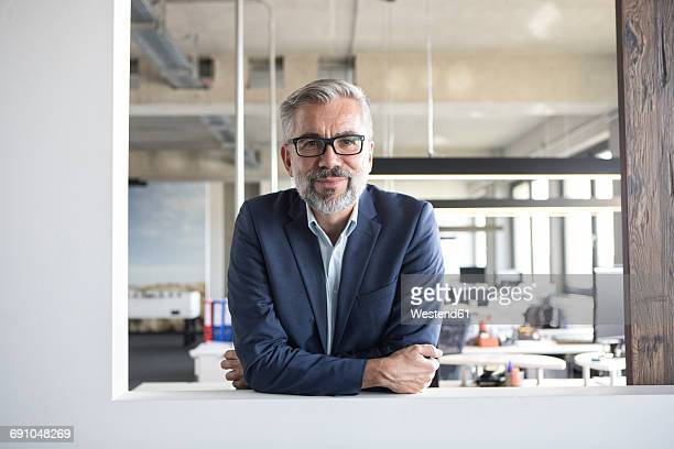 portrait of confident businessman in office - geschäftsmann stock-fotos und bilder