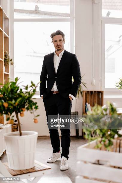 portrait of confident businessman in office - hands in pockets stock pictures, royalty-free photos & images