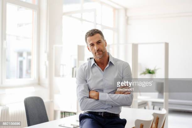 portrait of confident businessman in office - unternehmer stock-fotos und bilder