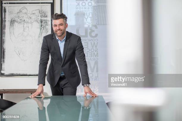 portrait of confident businessman in office - mid adult men stock-fotos und bilder