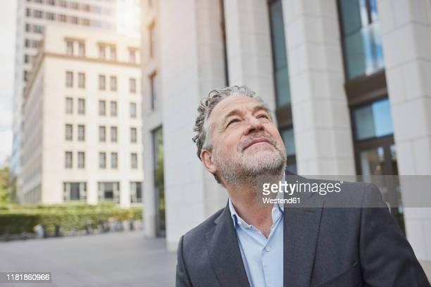 portrait of confident businessman in the city looking up - 55 59 jahre stock-fotos und bilder