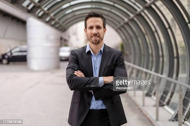 portrait of confident businessman in the city - bras croisés photos et images de collection