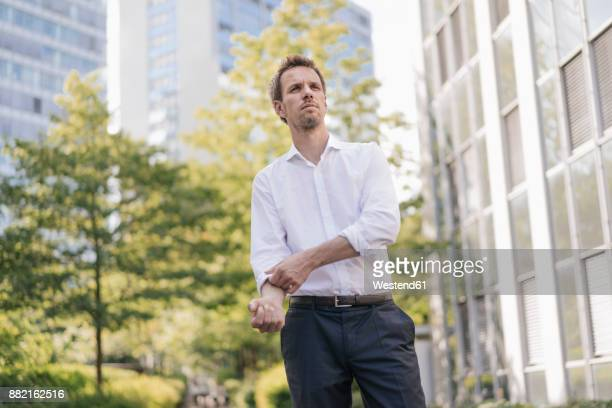 portrait of confident businessman in the city rolling up his sleeves - de rola imagens e fotografias de stock