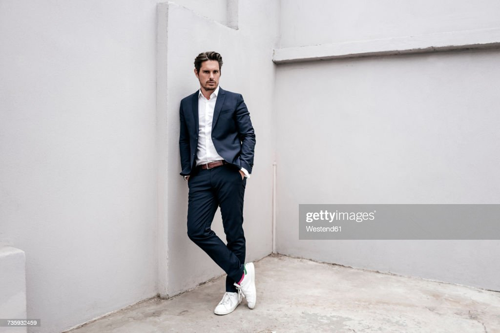 Portrait of confident businessman leaning against a wall : Foto de stock