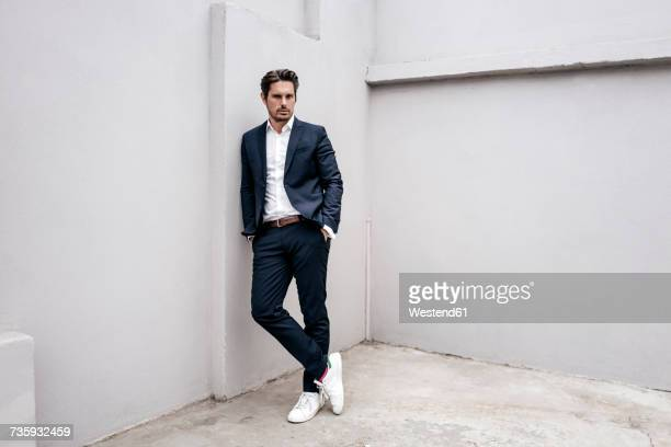 portrait of confident businessman leaning against a wall - mode stock-fotos und bilder