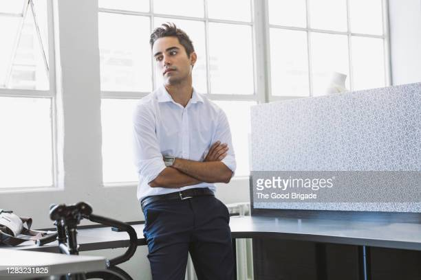 portrait of confident businessman leaning on desk in office - 20 24 years stock pictures, royalty-free photos & images