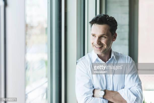 Portrait of confident businessman looking through window