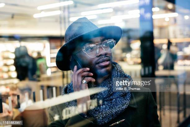 Portrait of confident businessman on cell phone behind windowpane