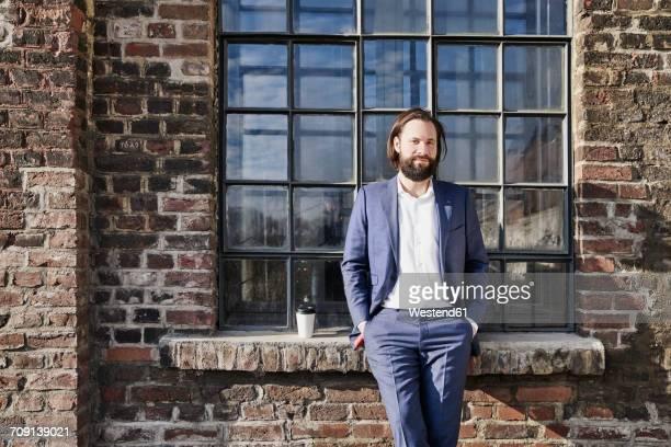 portrait of confident businessman outside brick building - pause machen stock-fotos und bilder