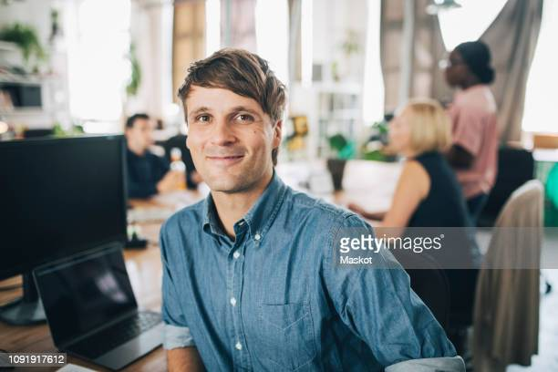 portrait of confident businessman sitting at desk in creative office - einzelner mann über 30 stock-fotos und bilder