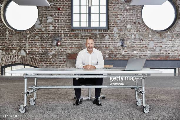 Portrait of confident businessman sitting at rolling table in a loft