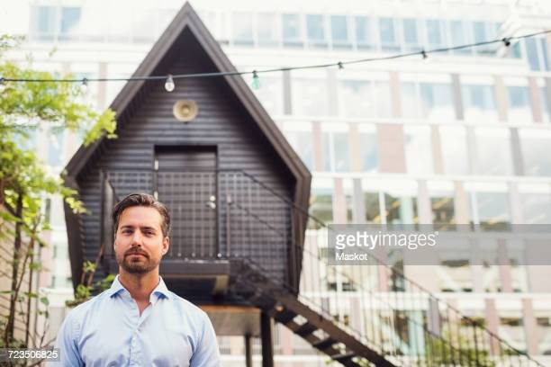 Portrait of confident businessman standing against log cabin at office yard