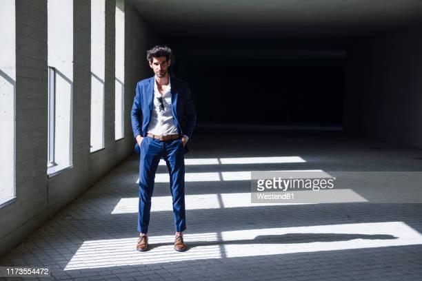 portrait of confident businessman standing in a passageway - herenkleding stockfoto's en -beelden