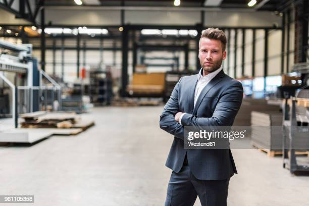 portrait of confident businessman standing on factory shop floor - dreiviertelansicht stock-fotos und bilder