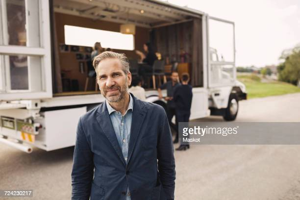portrait of confident businessman standing on road with colleagues and portable office truck in background - three quarter front view stock pictures, royalty-free photos & images