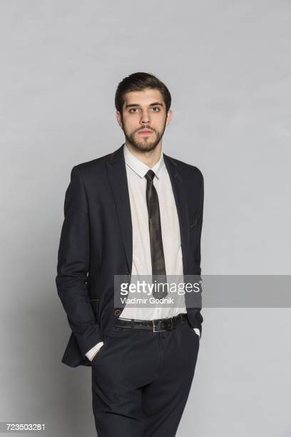 Portrait of confident businessman standing with hands in pockets against gray background