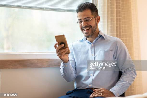 portrait of confident businessman using smart phone - one mature man only stock pictures, royalty-free photos & images