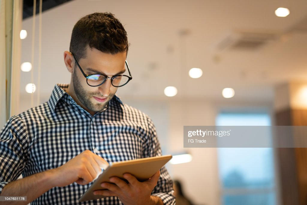 Portrait of Confident Businessman using tablet at office : Stock Photo