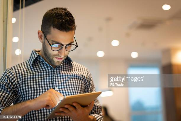 portrait of confident businessman using tablet at office - brazilian men stock photos and pictures