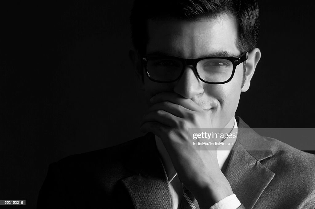 Portrait of confident businessman wearing glasses against black background : Stock Photo