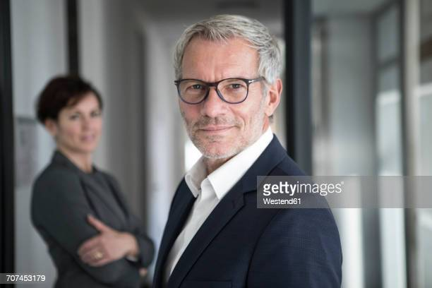 Portrait of confident businessman with businesswoman in background