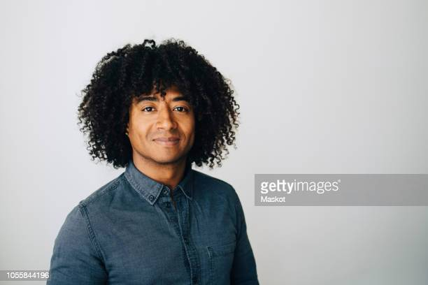 portrait of confident businessman with curly hair standing against white wall at creative office - waist up stock pictures, royalty-free photos & images
