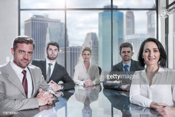 Portrait of confident businessmen and businesswomen sitting in conference room