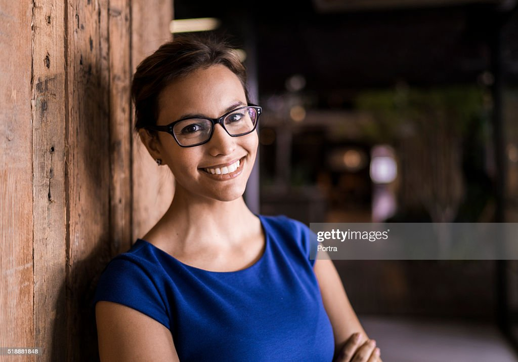 Portrait of confident businesswoman against wooden wall : Stock Photo