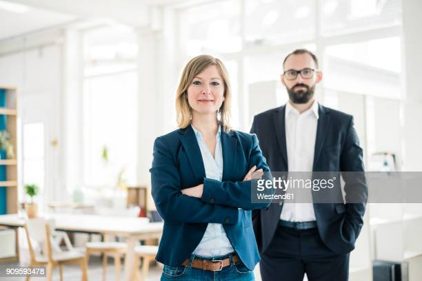 Portrait of confident businesswoman and man in office