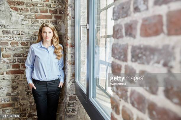 Portrait of confident businesswoman at brick wall