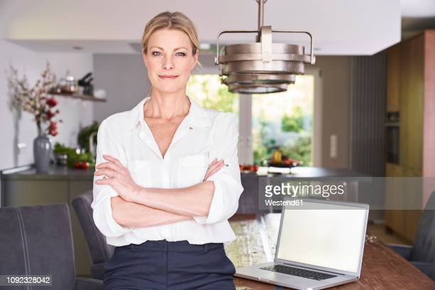 portrait of confident businesswoman at home with laptop on table - blouse stockfoto's en -beelden