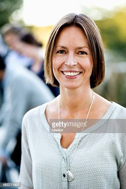 Portrait of confident businesswoman at patio with colleagues in background