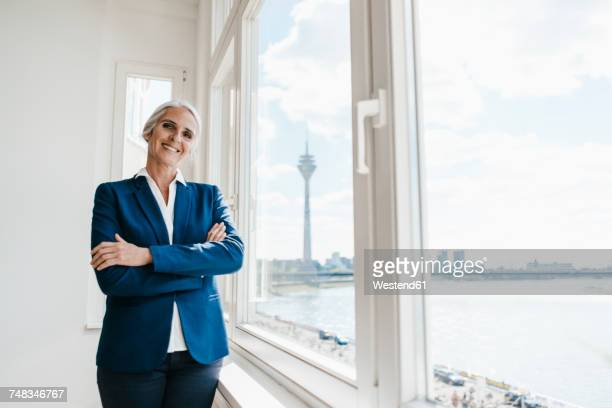 Portrait of confident businesswoman at the window in waterfront office