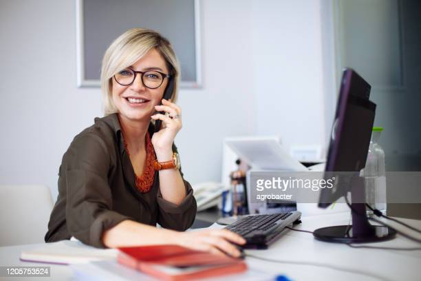 portrait of confident businesswoman at workplace - bank manager stock pictures, royalty-free photos & images